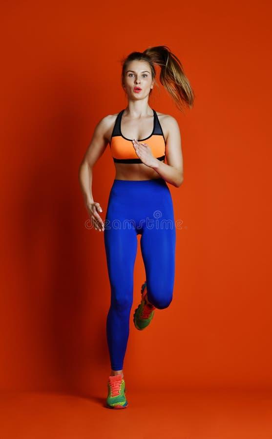Corredor da mulher na silhueta isolada no fundo vermelho movimento dinâmico Esporte e estilo de vida saudável imagens de stock royalty free
