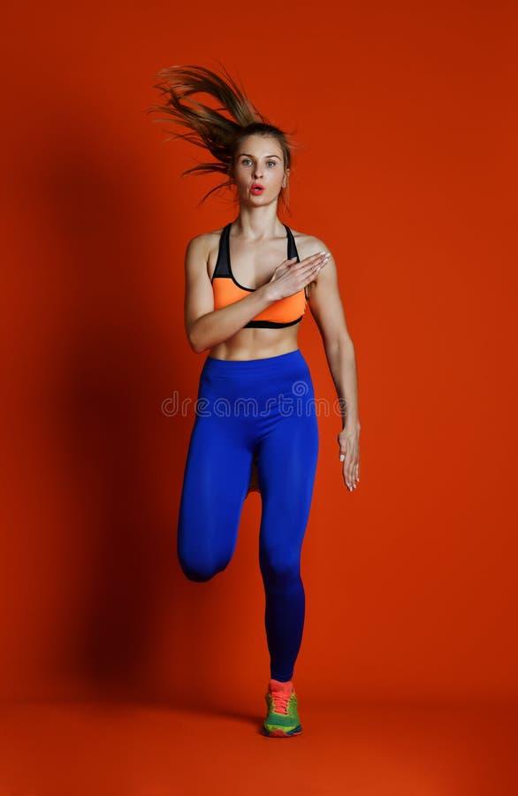 Corredor da mulher na silhueta isolada no fundo vermelho movimento dinâmico Esporte e estilo de vida saudável foto de stock royalty free