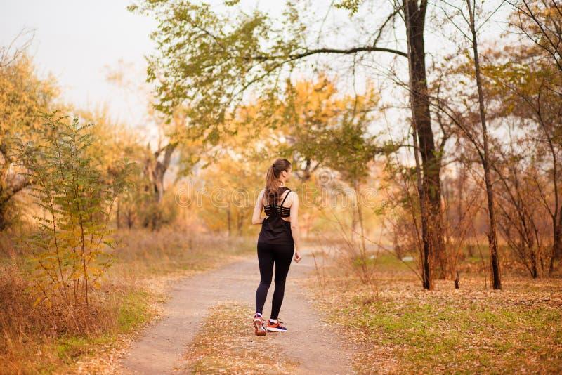 Corredor da mulher no conceito saudável da floresta da queda do outono imagem de stock royalty free