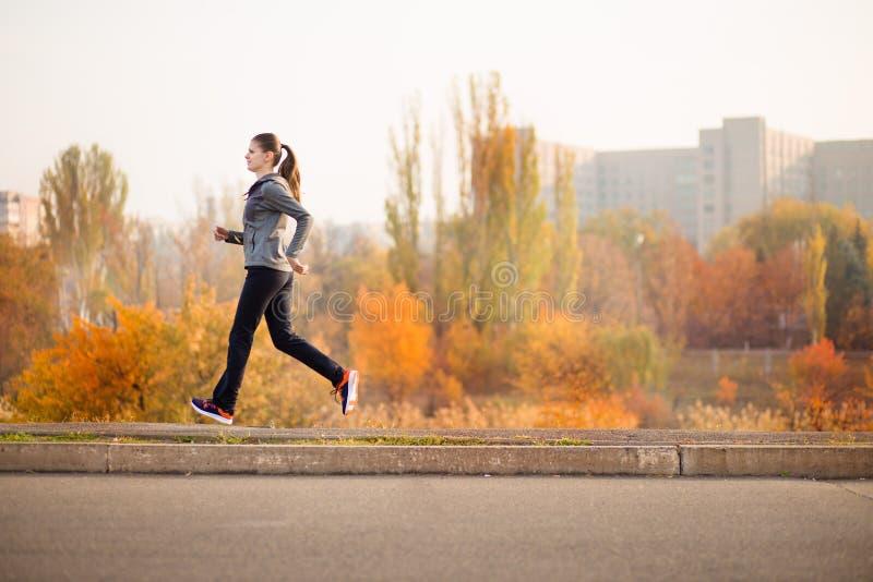 Corredor da mulher no conceito saudável da floresta da queda do outono imagem de stock