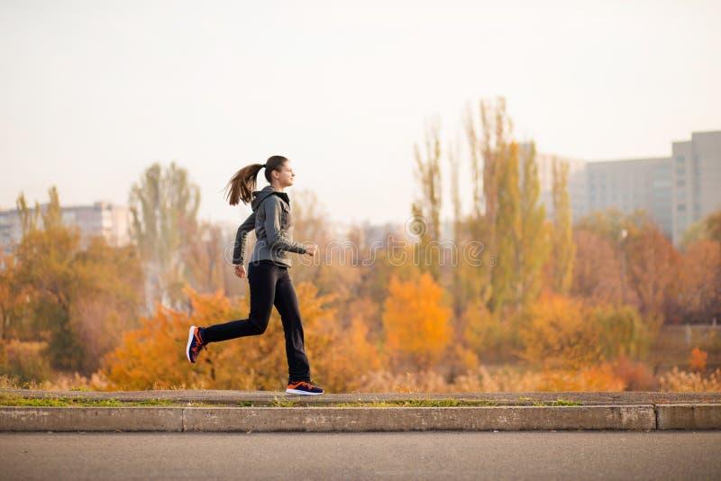 Corredor da mulher no estilo de vida saudável da floresta da queda do outono fotos de stock royalty free