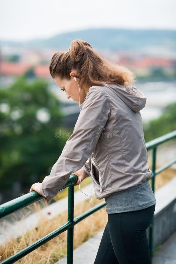 Corredor da mulher no perfil, inclinando-se contra o corrimão, olhando para baixo fotos de stock