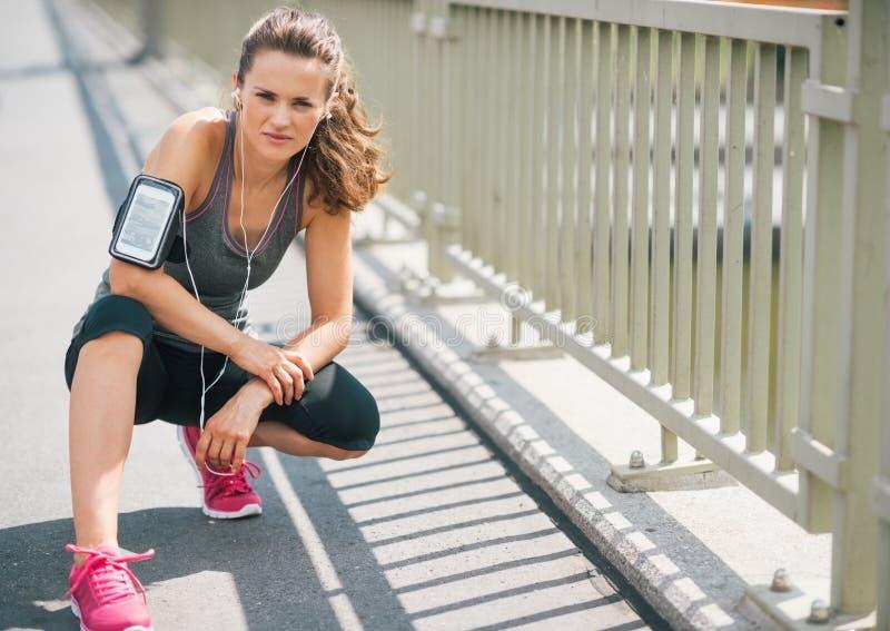 Corredor da mulher que ajoelha-se no passeio no verão no ajuste urbano fotografia de stock