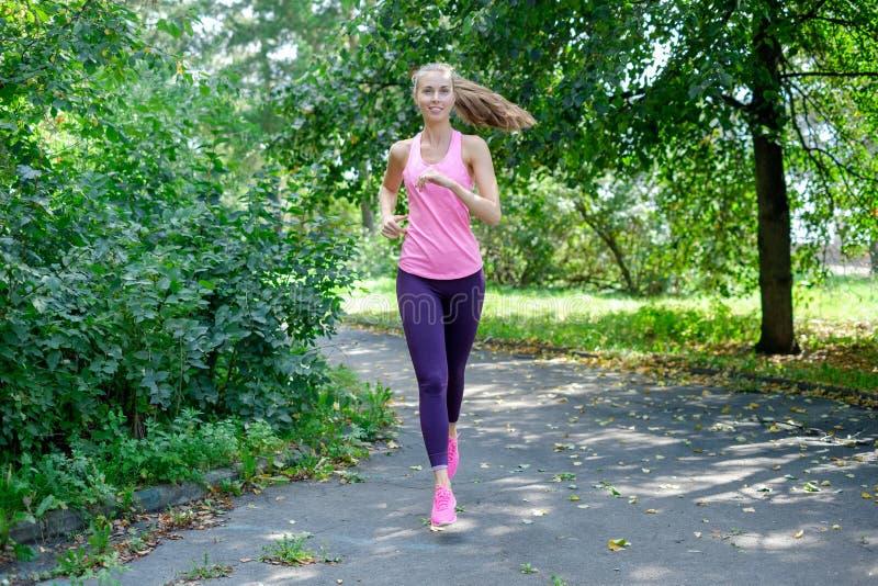 Corredor da mulher que corre através da estrada do parque da mola Exercício em um parque Menina bonita do ajuste Modelo da aptidã fotos de stock
