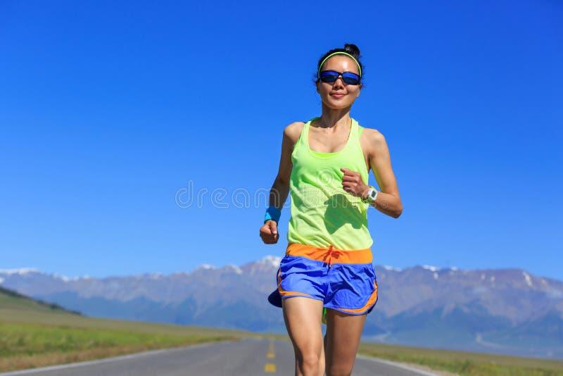 Corredor da mulher que corre na estrada fotografia de stock