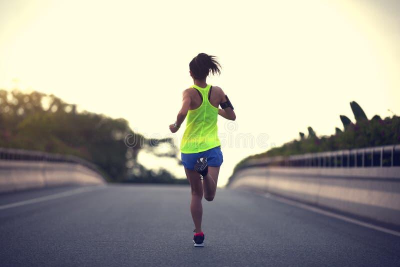 corredor da mulher que corre na estrada de cidade fotografia de stock
