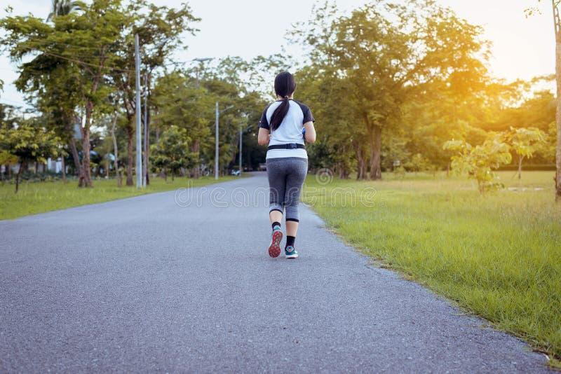 Corredor da mulher que corre na estrada no parque que movimenta-se na luz do nascer do sol foto de stock