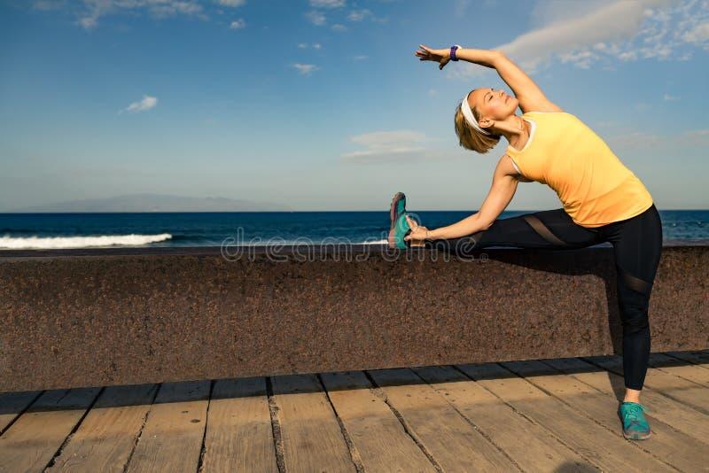 Corredor da mulher que estica no beira-mar no dia de verão ensolarado imagem de stock royalty free