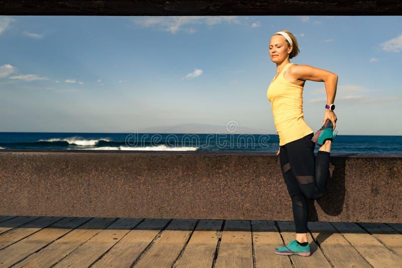 Corredor da mulher que estica no beira-mar no dia de verão ensolarado fotos de stock royalty free