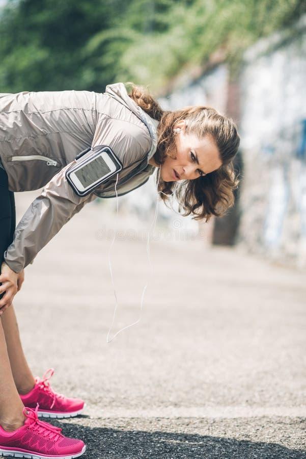 Corredor da mulher que inclina-se sobre o esticão para fora após uma corrida fotografia de stock royalty free