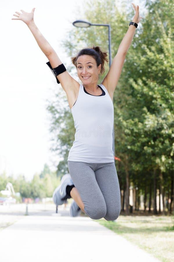 Corredor da mulher que salta para a alegria após ter ganhado a raça imagens de stock royalty free