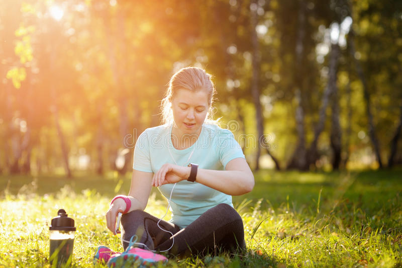 Corredor da mulher que senta-se na grama usando um relógio esperto imagem de stock