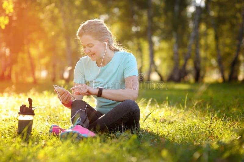 Corredor da mulher que senta-se na grama usando um telefone esperto imagem de stock royalty free