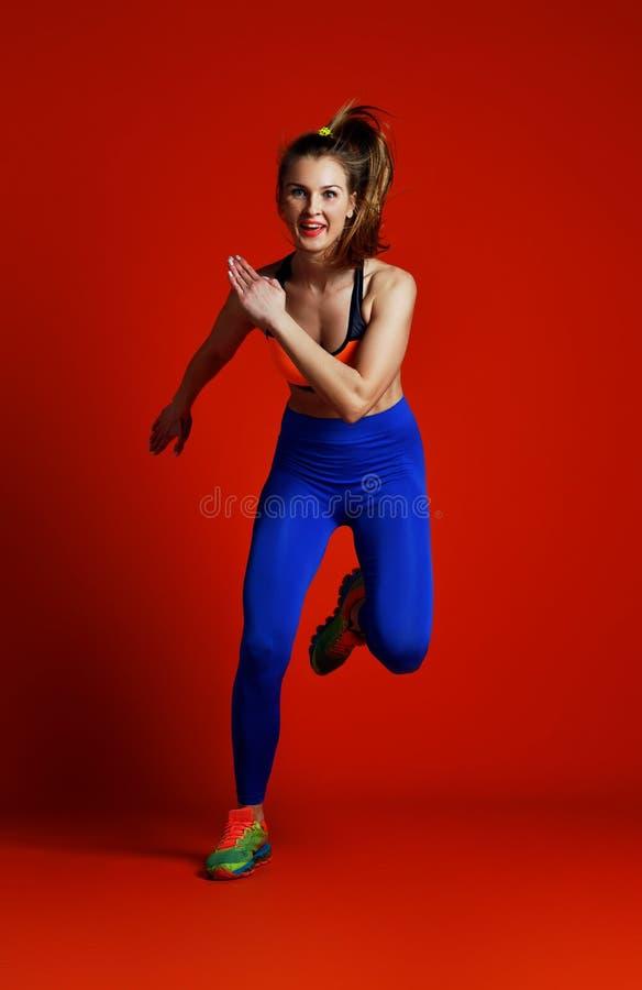 Corredor de la chica joven en la silueta aislada en fondo rojo fotografía de archivo