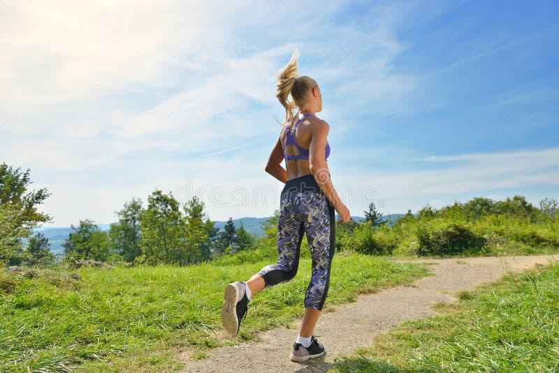 Corredor de la chica joven que activa en un rastro de montaña en el paisaje hermoso imagen de archivo