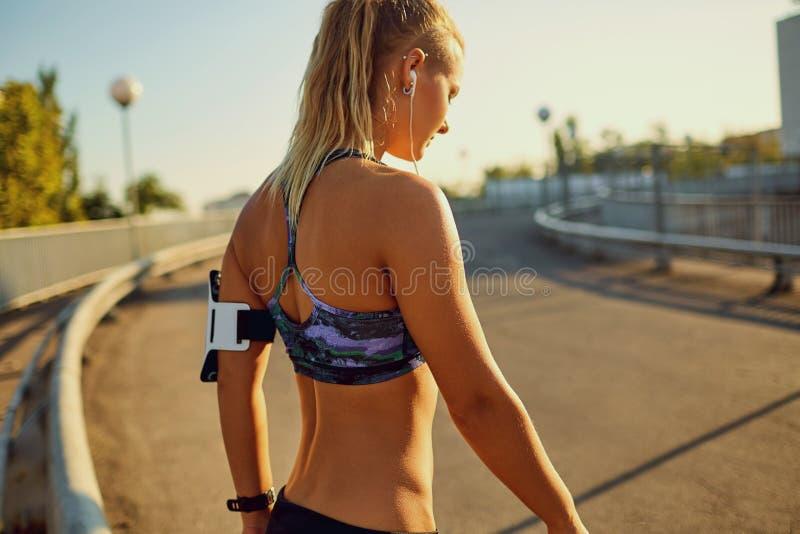 Corredor de la muchacha antes de activar en el camino en la ciudad en el verano imagen de archivo libre de regalías