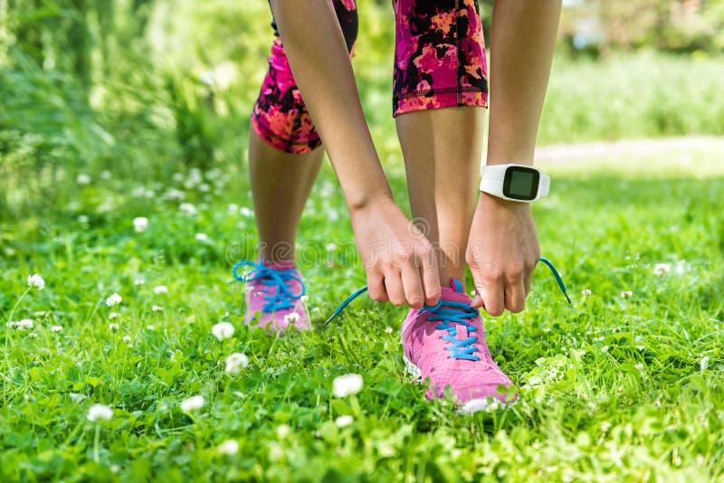 Corredor de la muchacha que ata pérdida de peso del verano de la zapatilla deportiva foto de archivo
