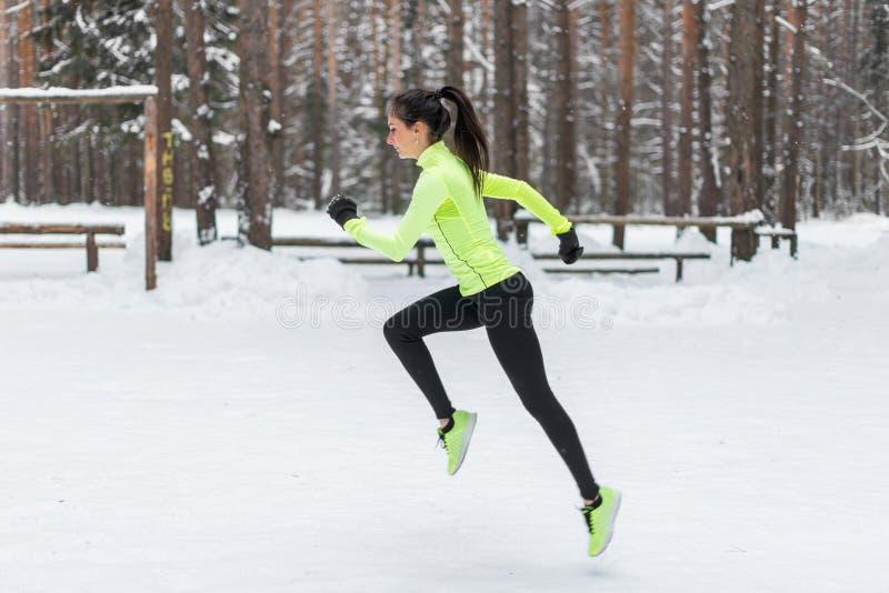 Corredor de la mujer del atleta que corre en tiempo que nieva frío El activar cardiio del maratón del entrenamiento de la calle foto de archivo libre de regalías