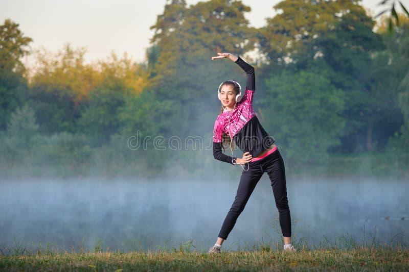 Corredor de la mujer en mañana de niebla cerca del lago imagenes de archivo