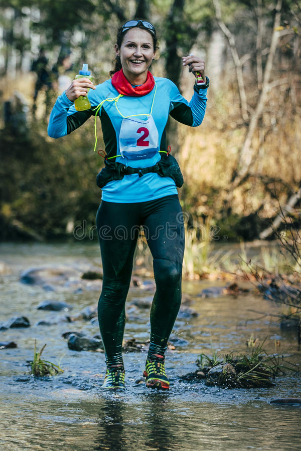 Corredor de la mujer joven que sonríe mientras que cruza un río de la montaña imagenes de archivo