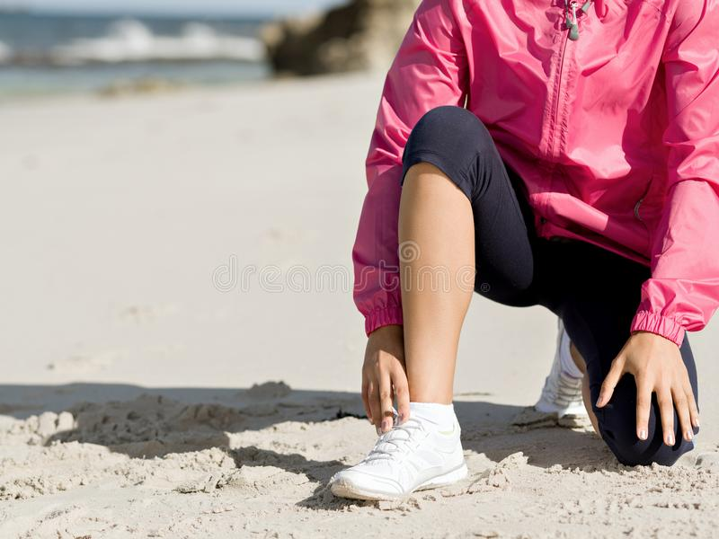 Corredor de la mujer que ata el cordón en la playa foto de archivo