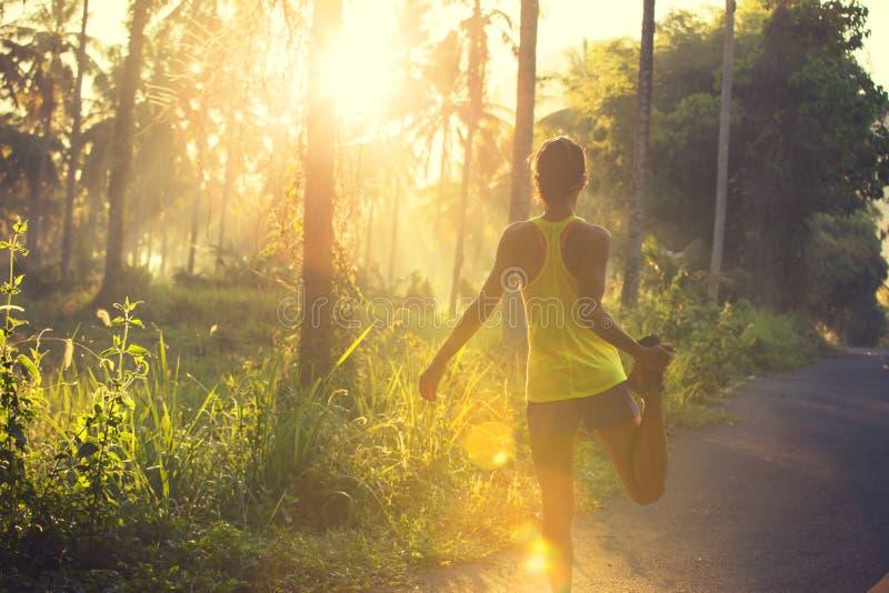 Corredor de la mujer que calienta en rastro del bosque de la salida del sol foto de archivo