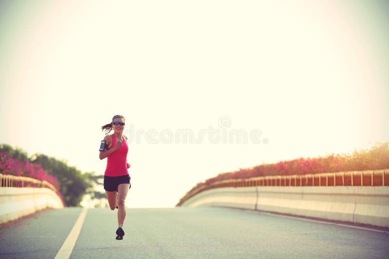 Corredor de la mujer que corre en el camino del puente de la ciudad foto de archivo