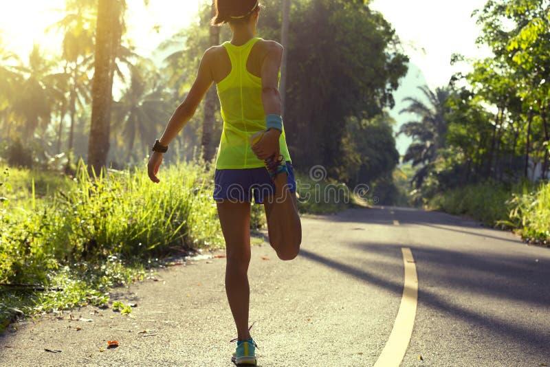 Corredor de la mujer que estira las piernas antes de correr en el rastro tropical del bosque de la mañana foto de archivo