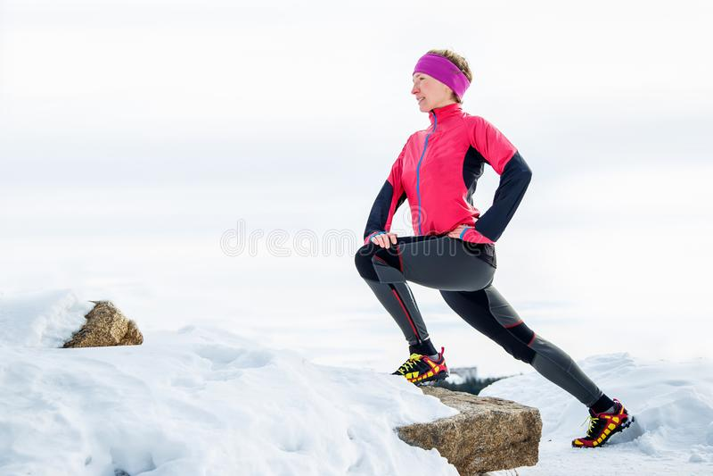 Corredor de la mujer que estira las piernas antes de funcionamiento Elaboración joven de la mujer del atleta foto de archivo libre de regalías