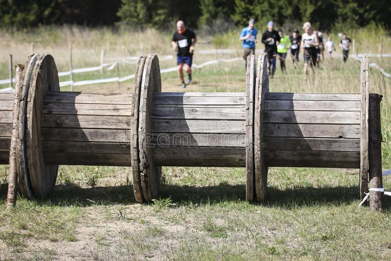 Corredor de raça enlameado do obstáculo na ação Corrida da lama imagens de stock