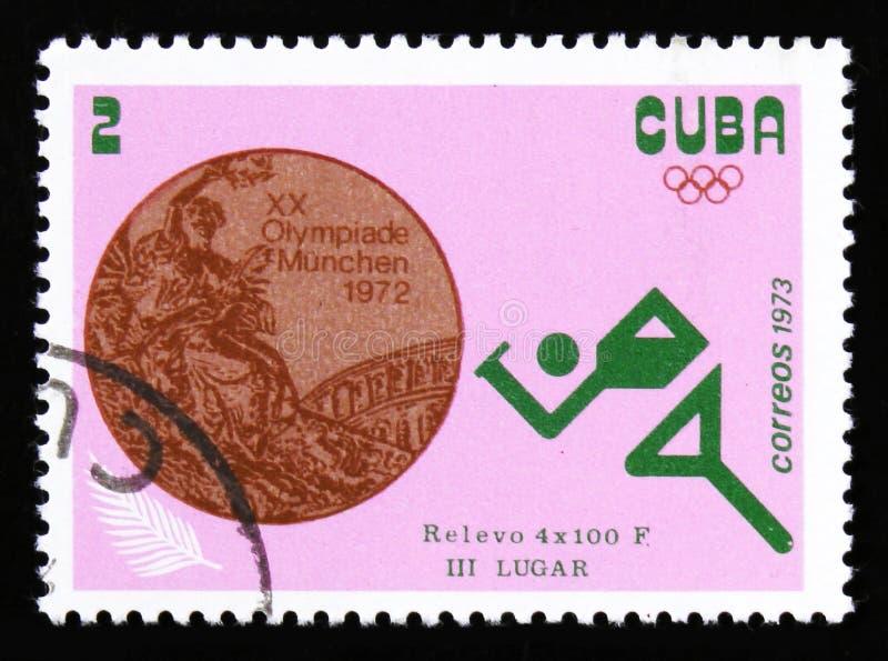 Corredor del atleta, con la raza de retransmisión de la inscripción 4x100 m de los Juegos Olímpicos del verano de la serie XX, Mu foto de archivo