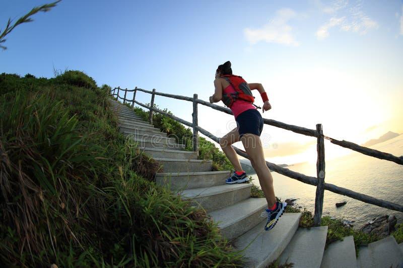 corredor del rastro de la mujer de la aptitud en las escaleras de la montaña de la playa imagen de archivo