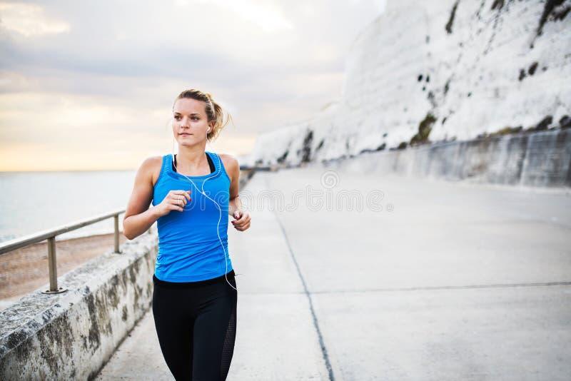 Corredor deportivo joven de la mujer con los auriculares que corren en la playa afuera imágenes de archivo libres de regalías