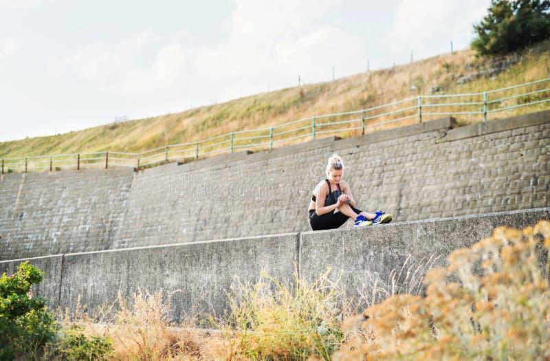 Corredor deportivo joven de la mujer que se sienta en un muro de cemento afuera, descansando imagen de archivo