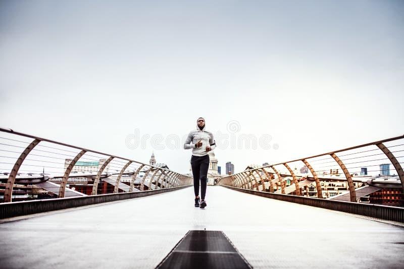 Corredor deportivo joven del hombre negro que corre en el puente afuera en una ciudad fotos de archivo libres de regalías
