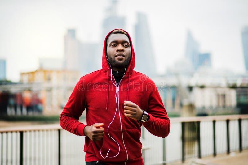 Corredor deportivo joven del hombre negro que corre en el puente afuera en una ciudad foto de archivo