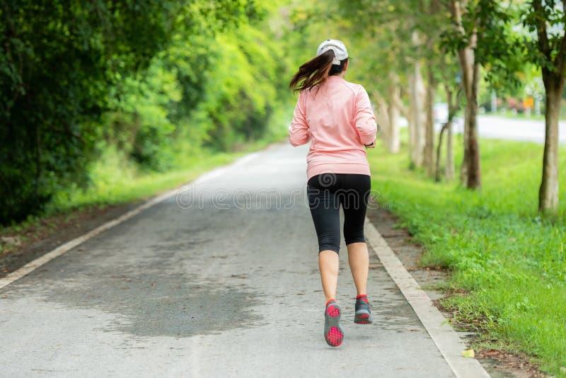 Corredor desportivo da mulher que corre através da estrada Exerc?cio em um parque Exerc?cio exterior em um parque fotos de stock royalty free