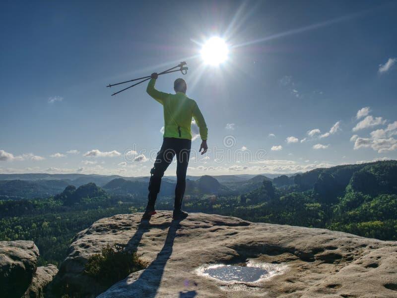 Corredor do atleta do homem com os polos trekking que correm a fuga rochosa fotos de stock royalty free