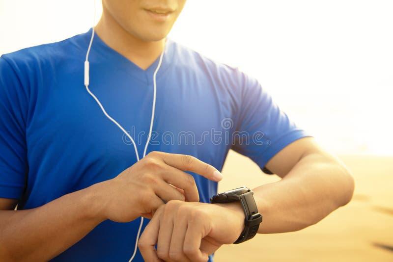 Corredor do homem na praia e verificação do relógio de Rate Monitor On do coração imagens de stock