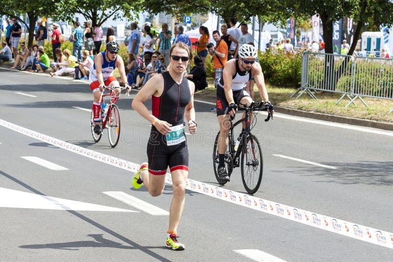Corredor e ciclistas durante a primeira raça de Szczecin do Triathlon imagem de stock royalty free
