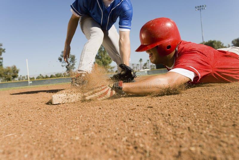 Corredor e jogador de campo que alcançam a base imagem de stock royalty free