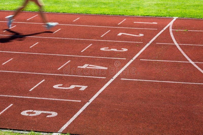 Corredor em uma pista de atletismo que termina uma raça primeiramente fotografia de stock