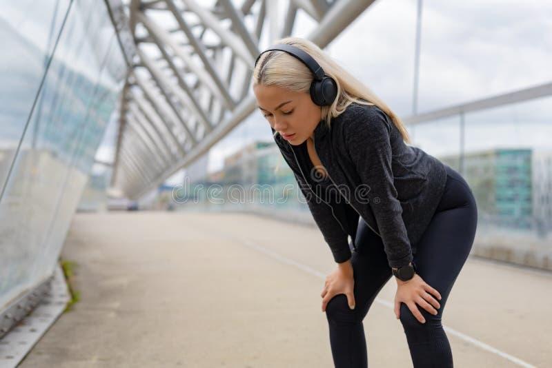 Corredor fêmea cansado que descansa com mãos em joelhos após o exercício fotografia de stock