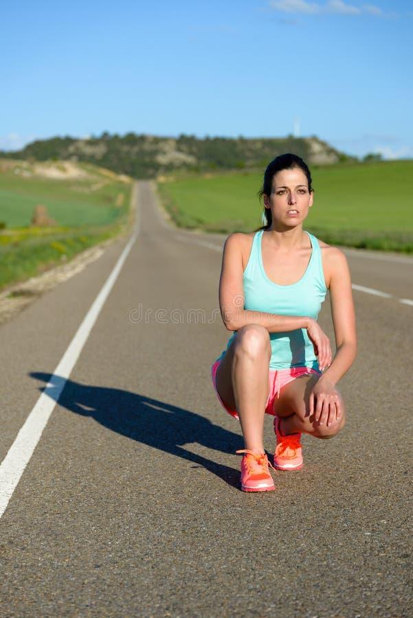 Corredor fêmea que descansa no treinamento da estrada foto de stock royalty free