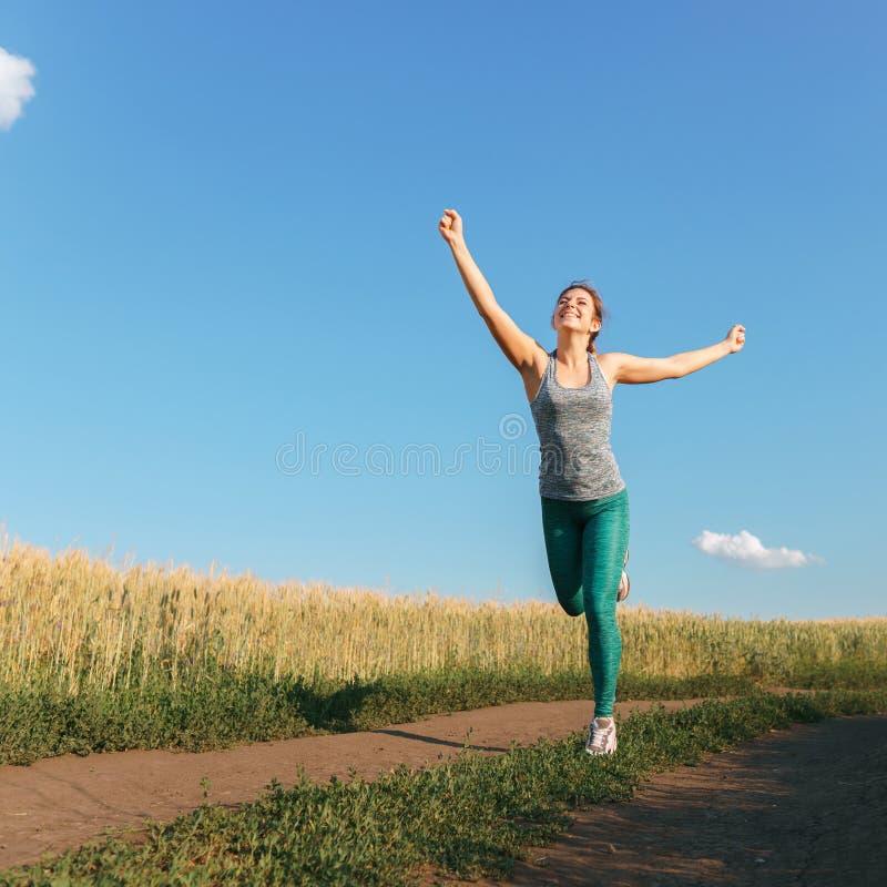 Corredor feliz de la mujer que aumenta ganar de los brazos fotos de archivo