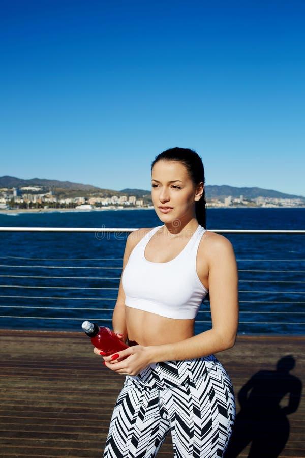 Corredor femenino atlético que toma la rotura después de sacudida larga por la playa que lleva a cabo la bebida de la energía en  imagen de archivo libre de regalías