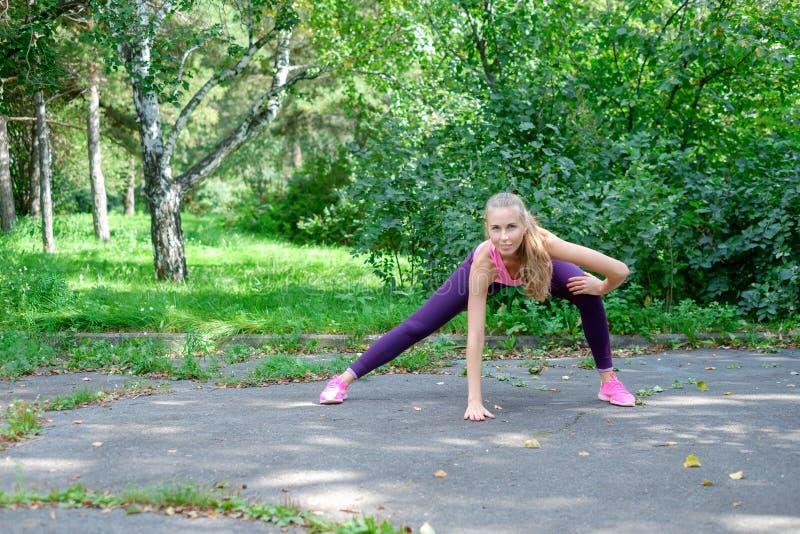 Corredor femenino con la figura hermosa que hace estirando ejercicio imagen de archivo