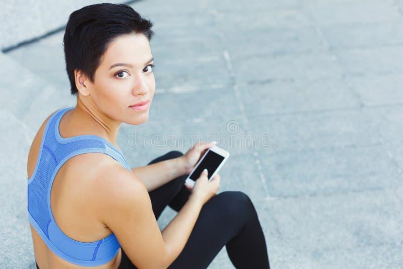 Corredor femenino con smartphone en las escaleras fotografía de archivo