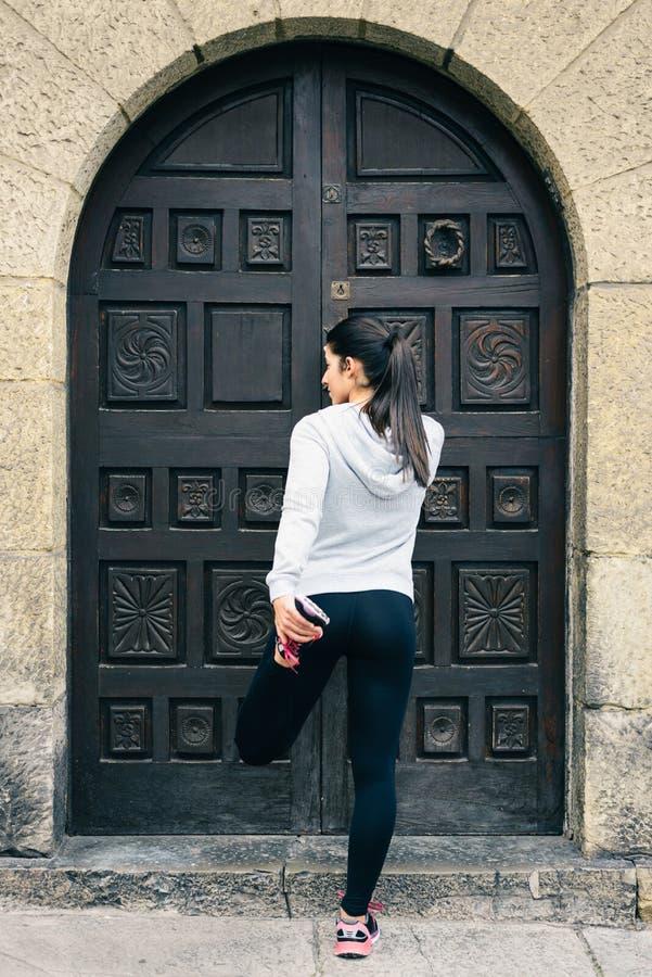 Corredor femenino del ajuste urbano que estira las piernas fotografía de archivo