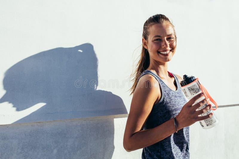 Corredor femenino feliz que celebra la botella de agua y la sonrisa foto de archivo